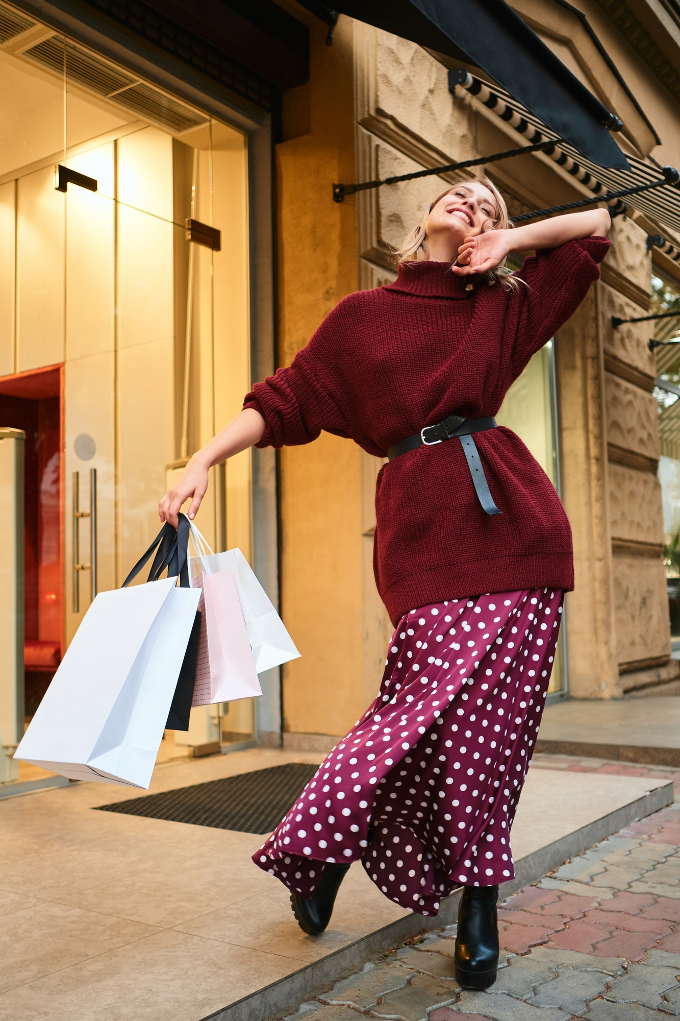 Pretty cheerful stylish blond girl with shopping bags rejoicing after shopping outdoor